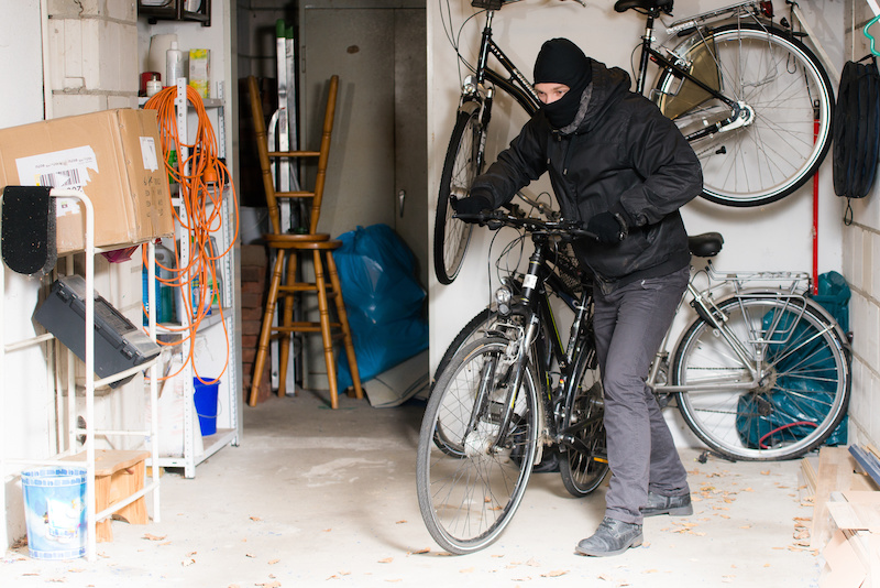 A man steals a bicycle from a garage that had an open door