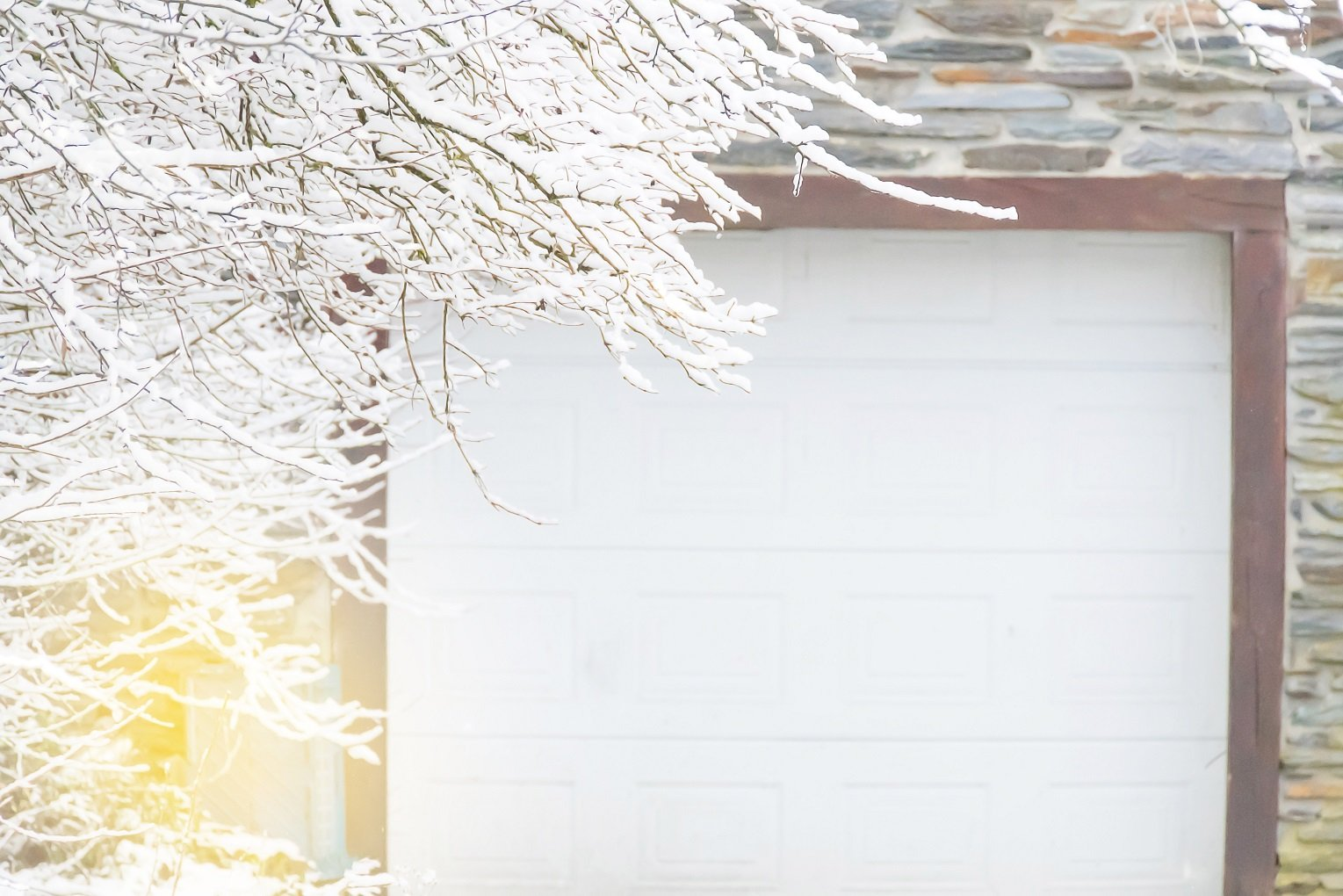 Non focus scene winter season with branch of tree cover with white snow with background background door of garage and brick wall best time for garage door maintenance