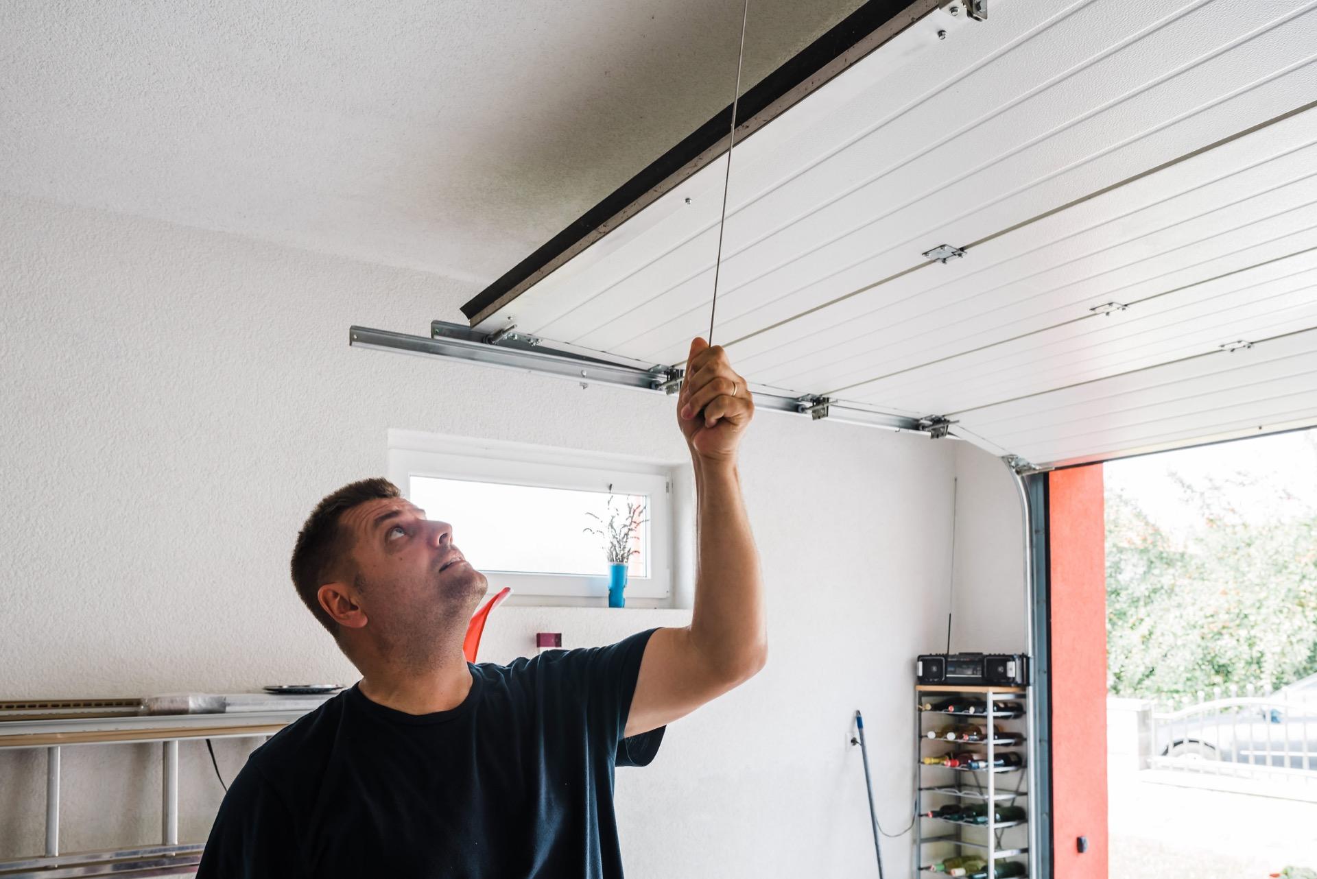 Man opening manual garage door from inside garage